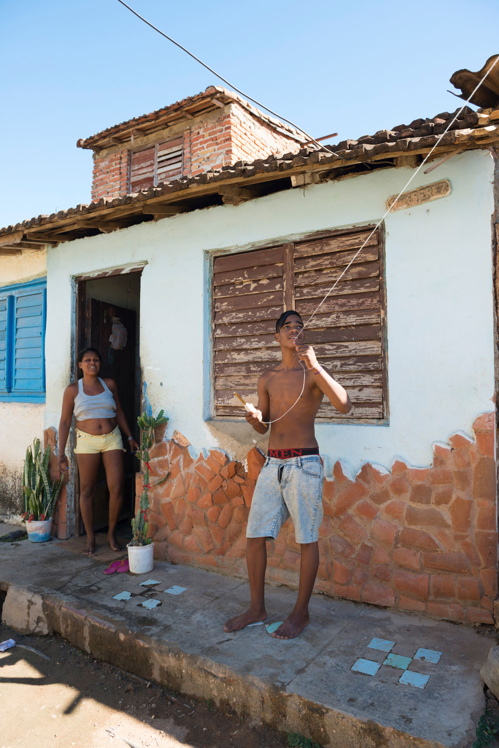 Young man flying a kite outside home in Trinidad,Cuba